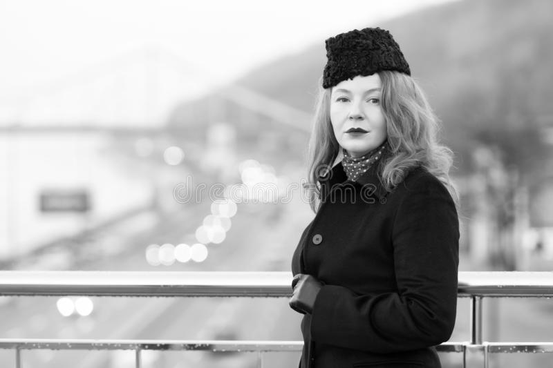 Mittlere Greisin im schwarzen Mantel auf Brücke Portrait der städtischen Frau stockfotografie