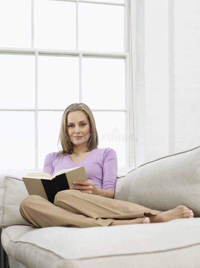Mittlere Greisin mit Buch auf Sofa stockbild
