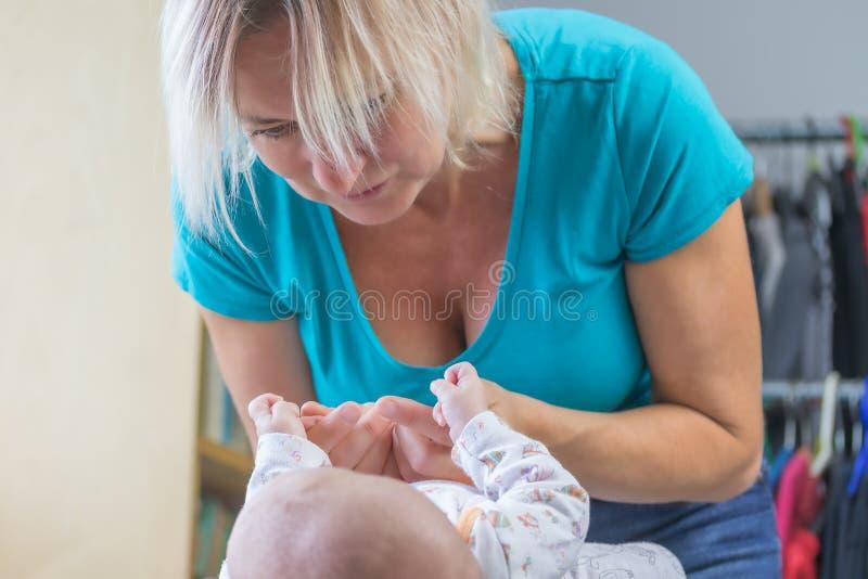 Mittlere Greisin spielt mit einem neugeborenen Baby stockbild