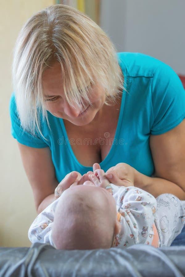 Mittlere Greisin spielt mit einem neugeborenen Baby stockfotografie
