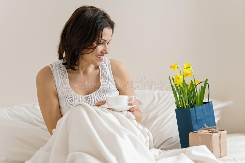 Mittlere Greisin wird mit Geschenk, der Blumenstrauß von Blumen gefallen und sitzt am Morgen im Bett mit Tasse Kaffee Gefühl des  stockfoto