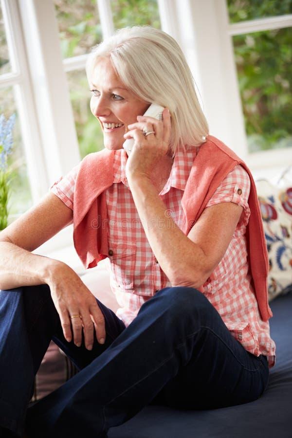 Mittlere Greisin zu Hause, die am Telefon spricht stockfoto