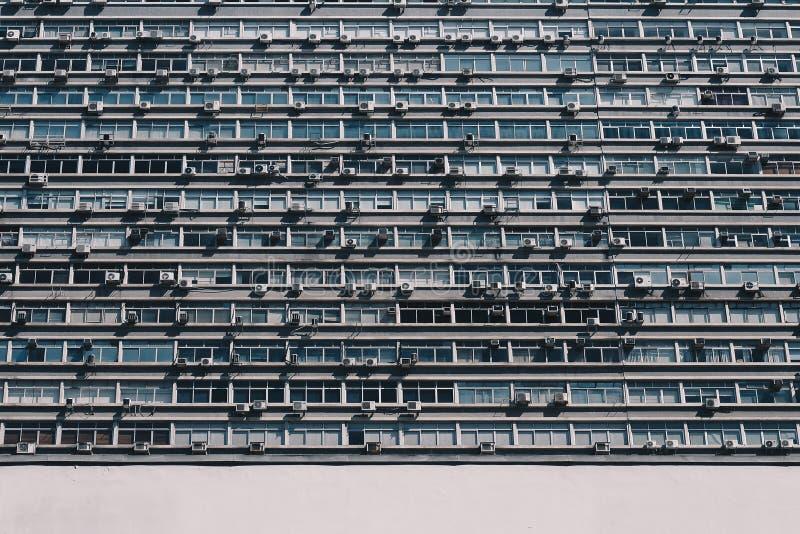 Mittlere Nahaufnahme des niedrigen Winkels geschossen von einem Wohngebäude mit vielen Fenstern und Klimaanlagen lizenzfreie stockfotografie