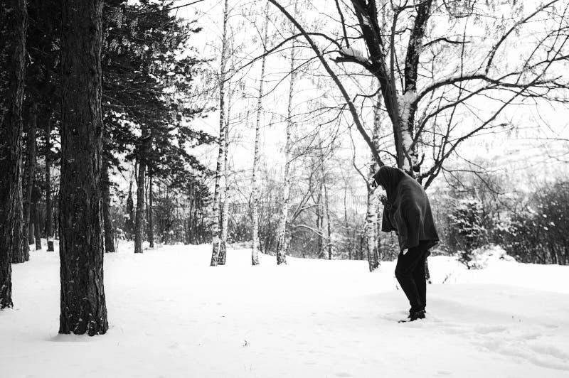 Mittlere Osten oder afrikanischer Flüchtling geht durch schneebedeckten Wald auf der Balkanroute lizenzfreies stockbild