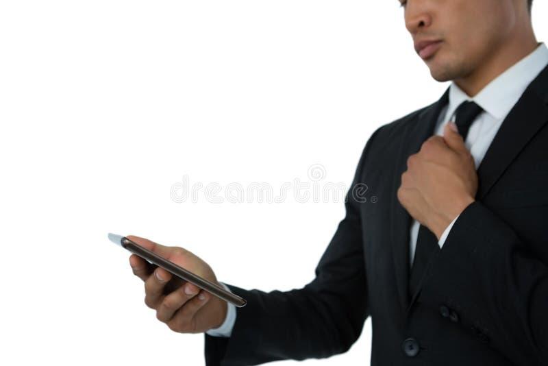 Mittlerer Abschnitt der Geschäftsmannholdingbindung bei der Anwendung des Handys stockfotografie