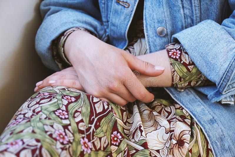 Mittlerer Abschnitt der tragenden Denimjacke der jungen Frau über Sommerkleid mit Blumenmuster stockbild