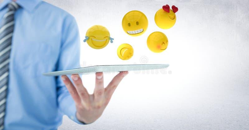 Mittlerer Abschnitt des Geschäftsmannes, der Tablette mit einer Hand und emojis gegen weiße Wand hält stock abbildung