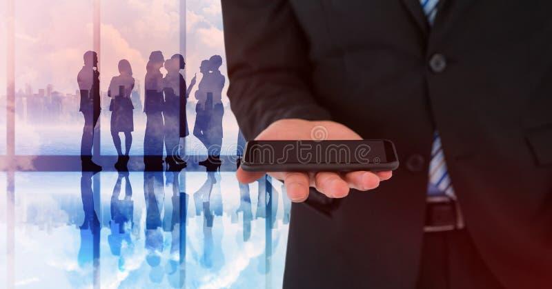 Mittlerer Abschnitt des Geschäftsmannes mit Telefon gegen Schattenbilder und Fenster lizenzfreies stockbild