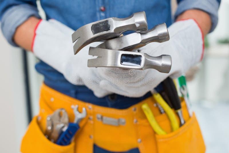 Mittlerer Abschnitt des Heimwerkers Hämmer mit toolbelt um Taille halten lizenzfreies stockfoto