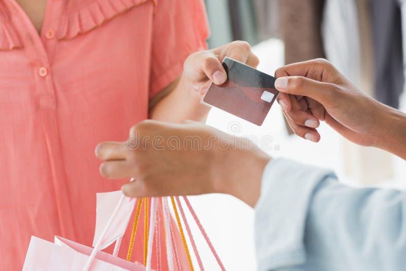 Mittlerer Abschnitt des Kunden Einkaufstaschen und Kreditkarte von der Verkäuferin empfangend stockbild