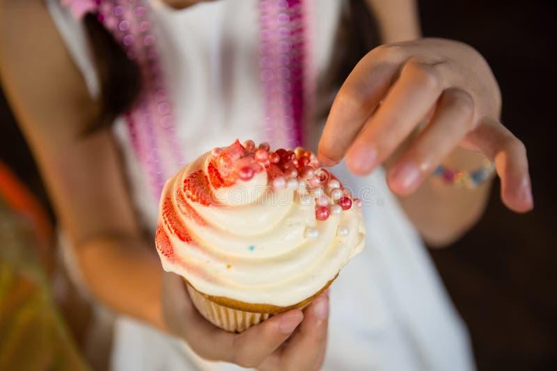 Mittlerer Abschnitt des Mädchens kleinen Kuchen während der Geburtstagsfeier verzierend lizenzfreies stockbild