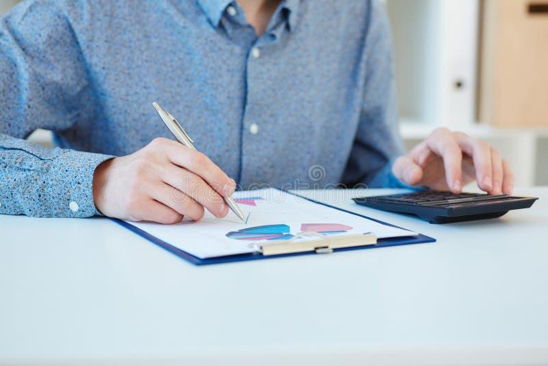 Mittlerer Abschnitt einer Mannanalysegeschäftsbuchhaltung Geschäftsdiagramme und -diagramme auf einem weißen hölzernen Schreibtis stockbilder