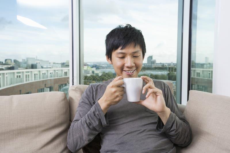 Mittlerer erwachsener Mann, der Kaffeetasse im Haus hält lizenzfreie stockfotos