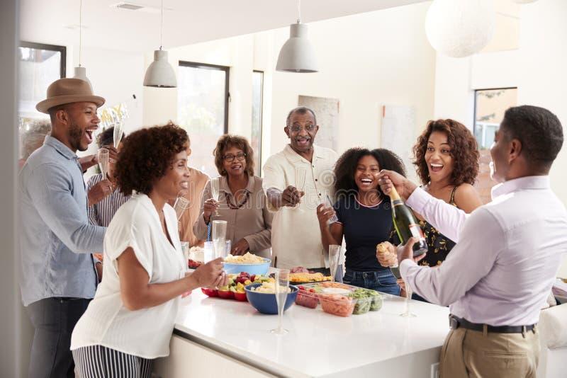 Mittlerer gealterter öffnender Champagner des Afroamerikanermannes, zum mit seiner Familie mit drei Generationen zu Hause zu feie stockbild
