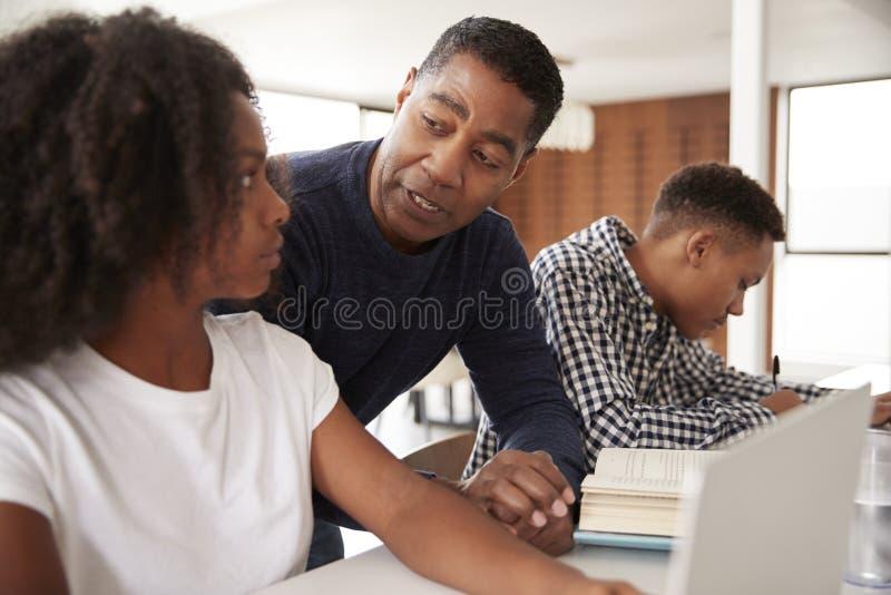 Mittlerer gealterter Afroamerikanervati, welche seinen jugendlich Kindern mit Hausarbeit, niedriger Winkel, Abschluss oben hilft stockfotos