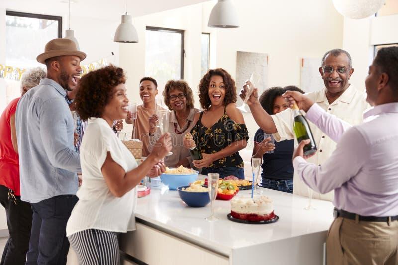 Mittlerer gealterter ?ffnender Champagner des Afroamerikanermannes, zum mit seiner Familie mit drei Generationen zu Hause zu feie stockfotografie