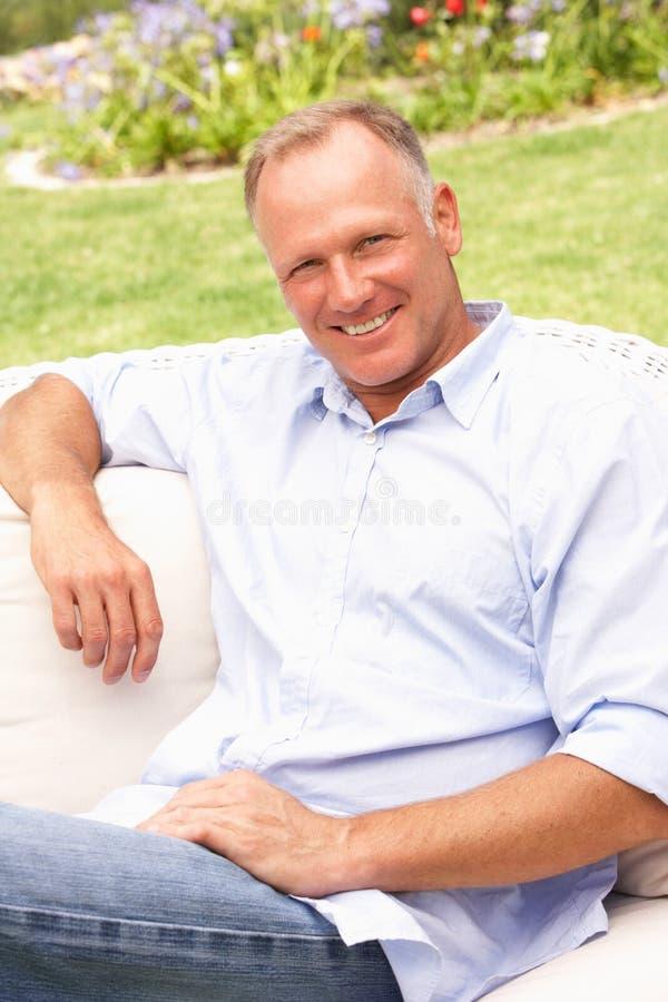 Mittlerer gealterter Mann, der im Garten sich entspannt stockfotografie