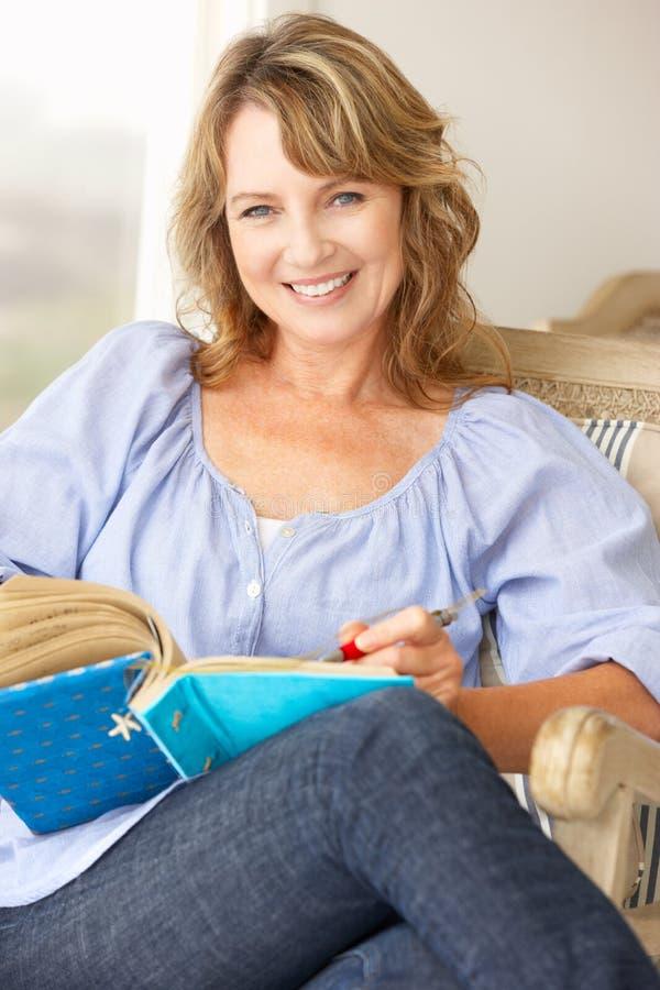 Mittleres Altersfrauenschreiben im Notizbuch stockbild