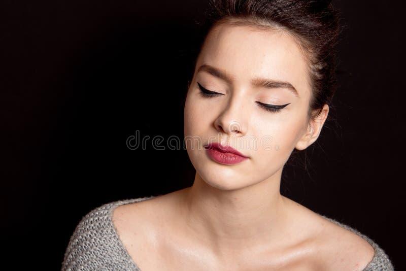Mittleres Brötchen der weiblichen Frisur mit den roten Lippen des braunen Haarmakes-up und perfekter Haut des schwarzen Pfeiles stockfotos