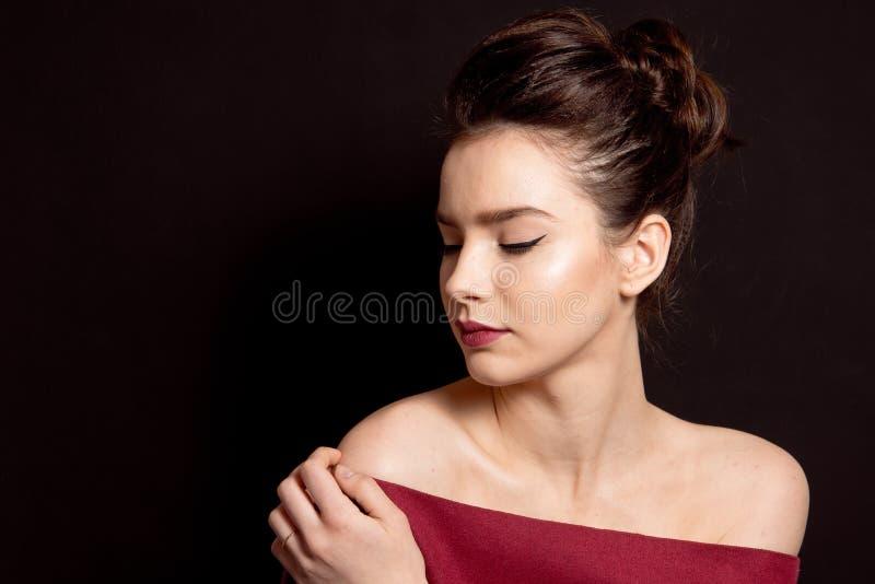 Mittleres Brötchen der weiblichen Frisur mit den roten Lippen des braunen Haarmakes-up und perfekter Haut des schwarzen Pfeiles lizenzfreies stockbild