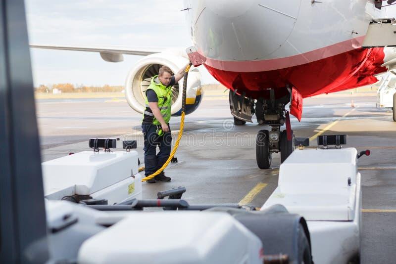 Mittleres erwachsenes Mannschaftsmitglied-Aufladungsflugzeug auf Rollbahn stockbild