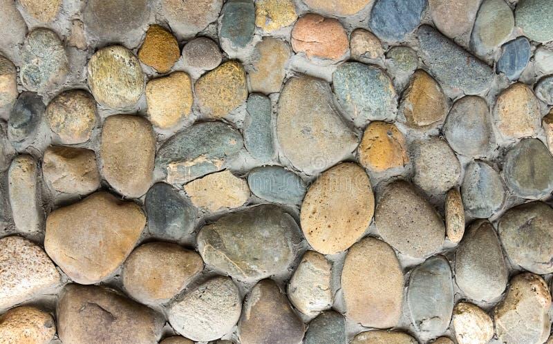 Mittleres Hintergrundteil des Steinkopfsteins des musters runden der Wand lizenzfreie stockfotos