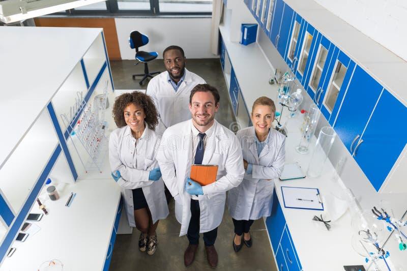 With Mix教授种族团体现代实验室油罐顶部角钢观点的科学家的In Lab医生微笑的队  免版税库存图片