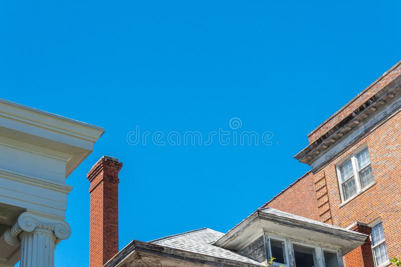 Mix of architecture with Ionic columns, abandoned house with very tall chimney, and brick apartment buildings royalty free stock images