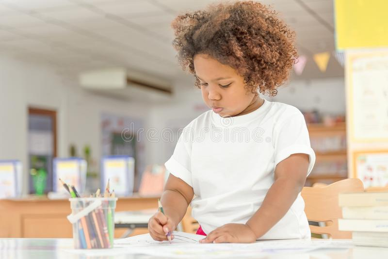 Mix Asian and African little toddler girl concentrate drawing in library. Child drawing on free time.  stock image