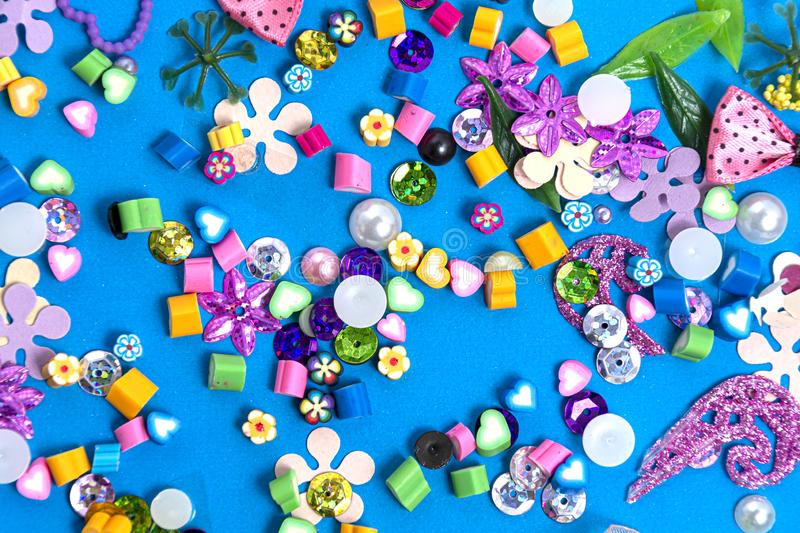 Mix of beads and beads on a blue background. Abstract colorful background. The concept of needlework, creativity and a hobby stock photo