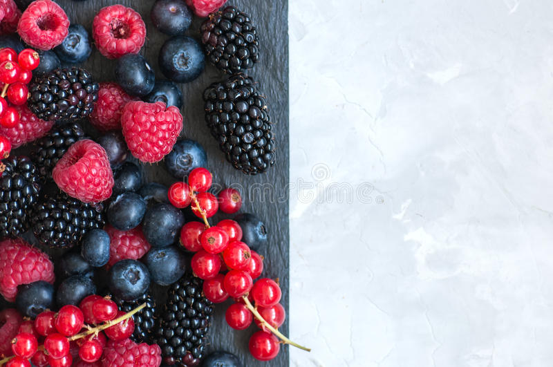 Mix of berries raspberries red currants blueberries and blackberries on black slate board. White stone background. Overhead view stock photography