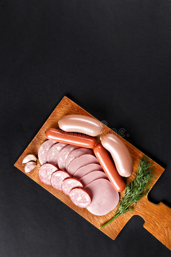 Mix of boiled sausage slices on cutting board stock photos
