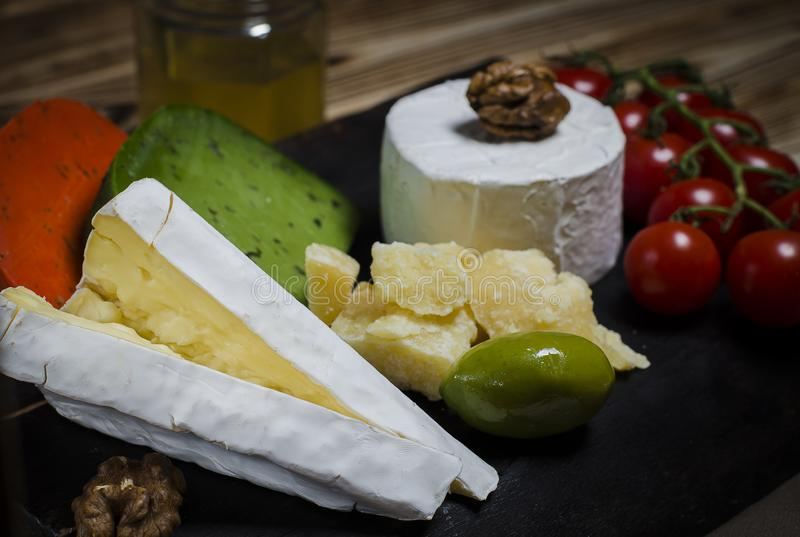 Mix cheese on dark background on wood board with grapes, honey, nuts, tomatoes and basil. Top view stock photos
