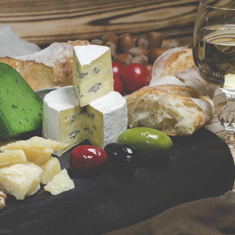 Mix cheese on dark background on wood board with grapes, honey, nuts, tomatoes and basil. Top view. Camembert, brie, parmesan cheese, green cheese with basil stock photos