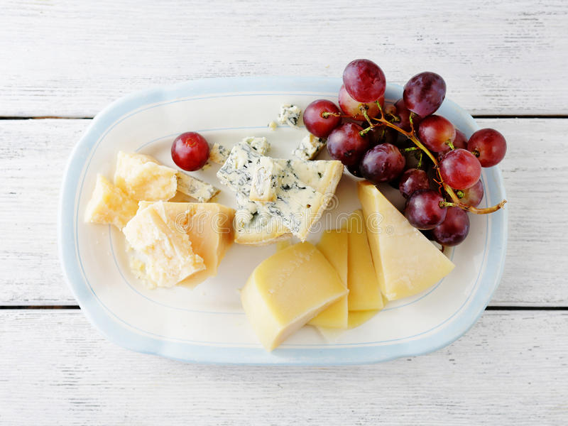 Mix cheeses with grapes. On plate royalty free stock photo