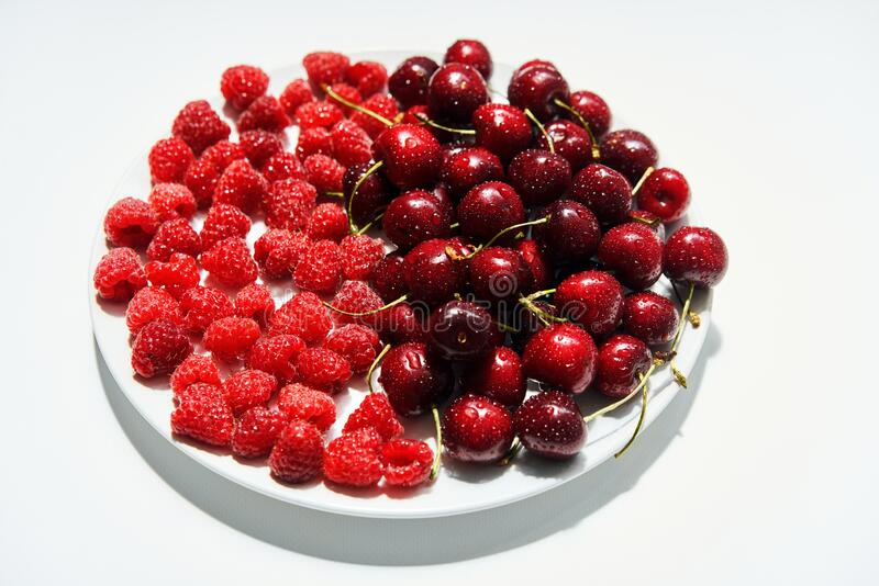 Mix of cherries and raspberries on plate isolated on white background stock image