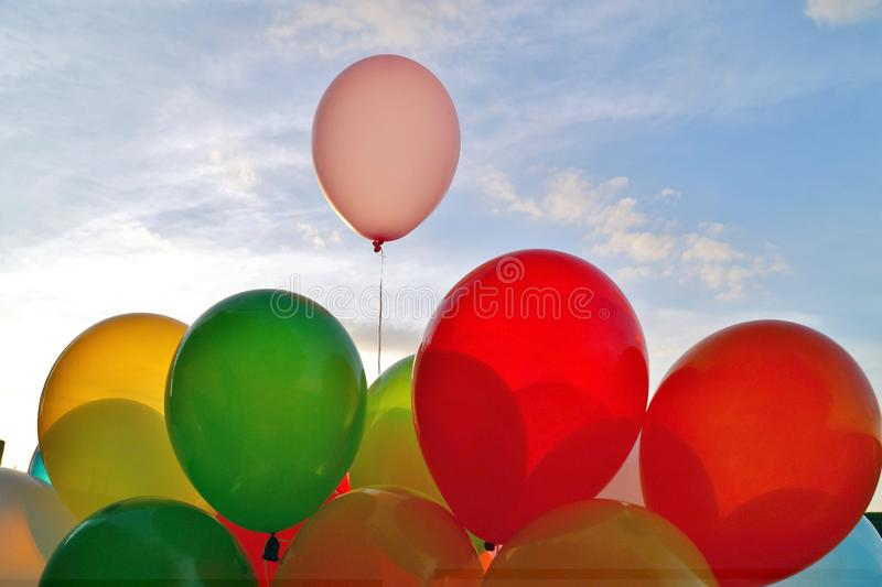 Mix of colorful balloons over blue sky background and sun shining through clouds. stock images