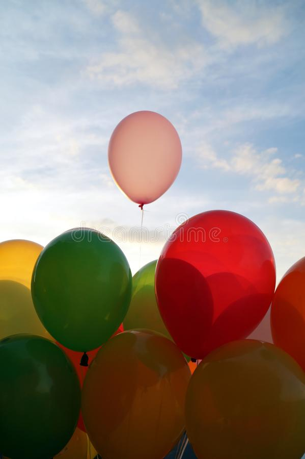 Mix of colorful balloons over blue sky background and sun shining through clouds, royalty free stock photography