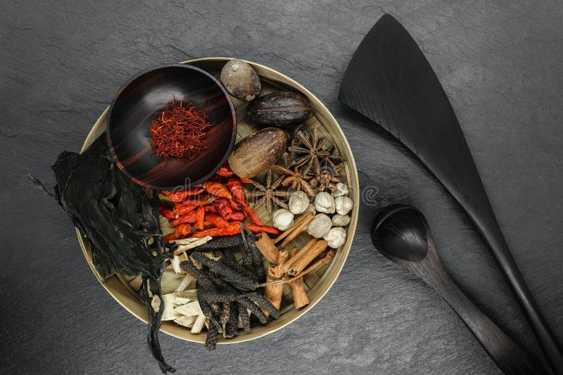 Mix composition of various exotic dried spices in natural bamboo bowl on black stone background royalty free stock photography