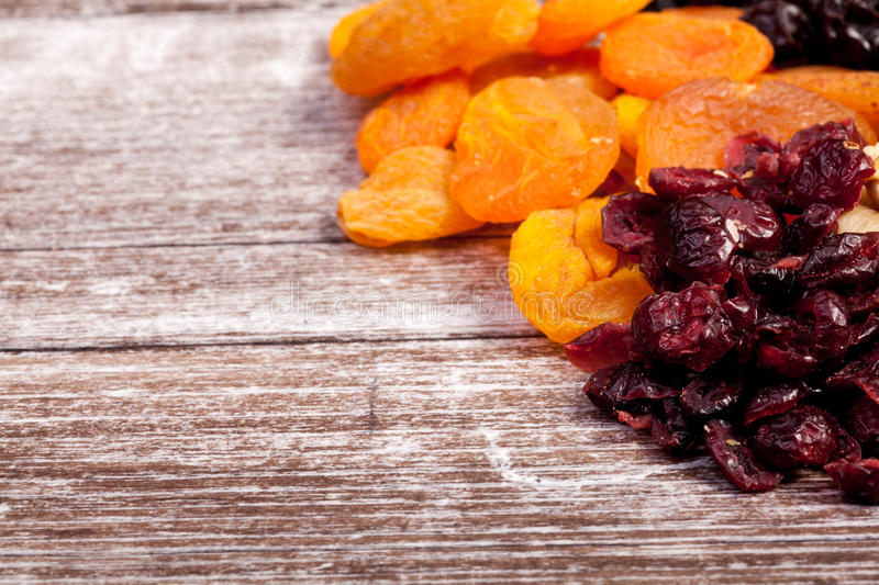 Mix of different dried fruits on wooden background royalty free stock photo