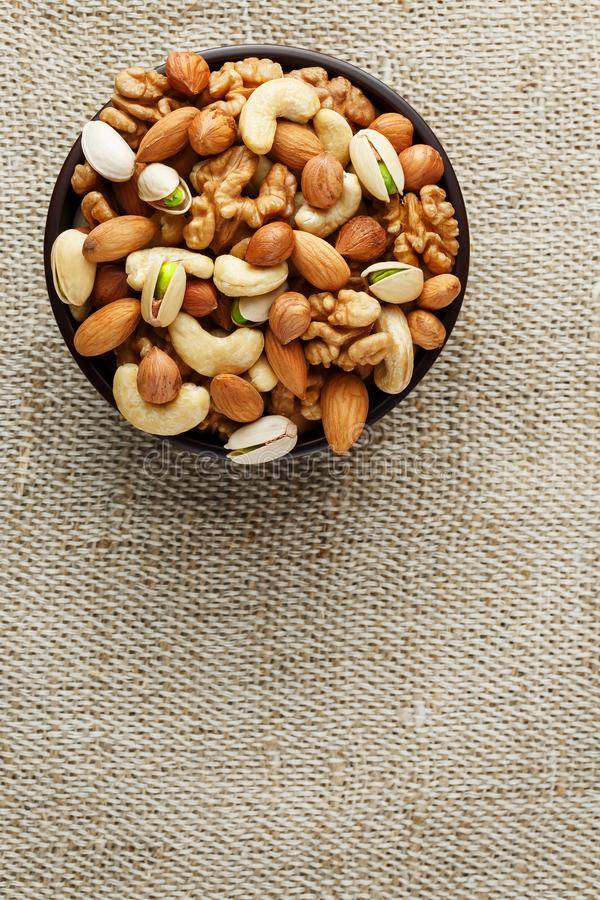 Mix of different nuts in a wooden cup against the background of fabric from burlap. Nuts as structure and background, macro. Top royalty free stock photo