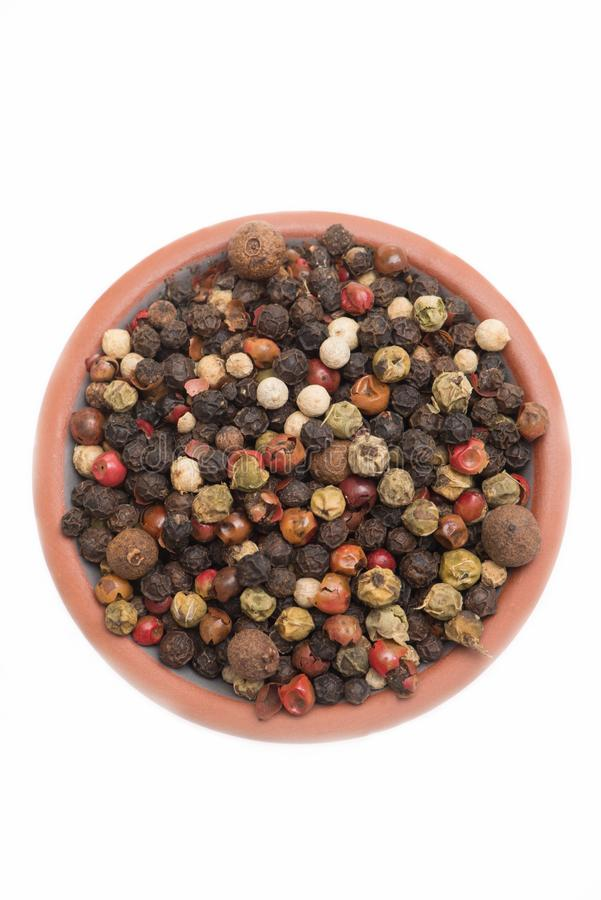 A mix of different peppercorns in a bowl, isolated on a white background stock image