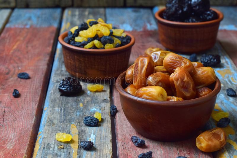 Mix of different varieties of dried fruits on wooden background - dates, apricots, prunes, raisins. Organic healthy food. Excellen royalty free stock photography