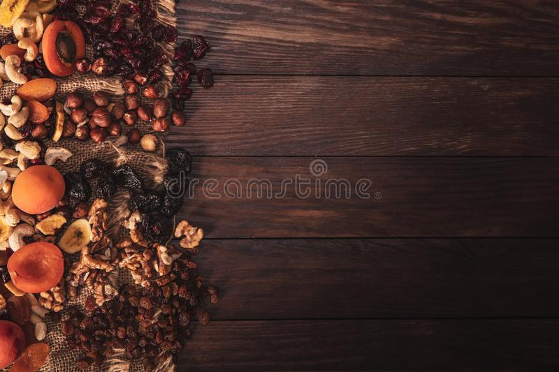 Mix of dried fruit and nuts arranged on linen fabric. And an old table. Composition in the old style with a view from the top and copy space for your text stock images