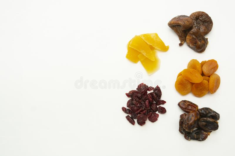 Mix of dried fruits heaps isolated on white background with copy space - figs, dates, mango, cranberries. Breakfast or snack, royalty free stock photo
