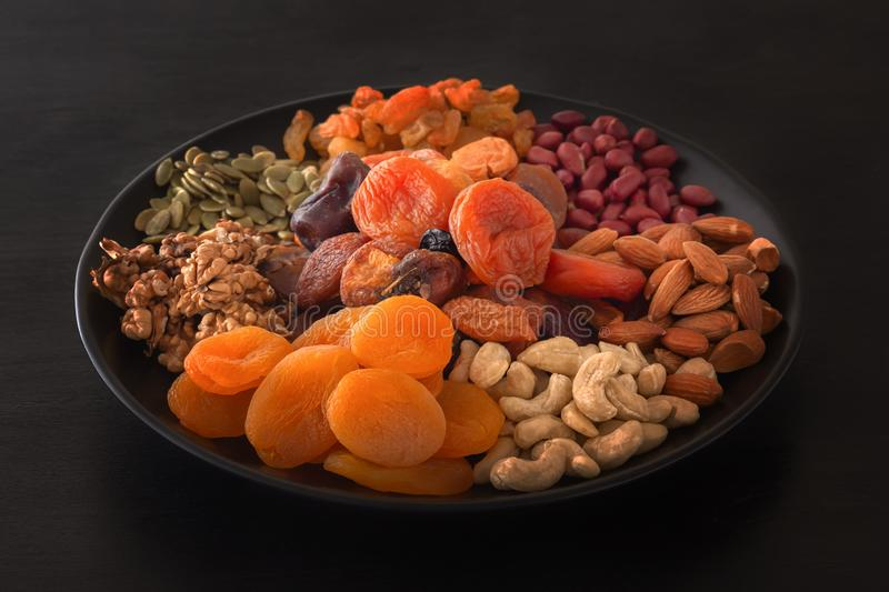 Mix of dried fruits and nuts on a black table royalty free stock photos