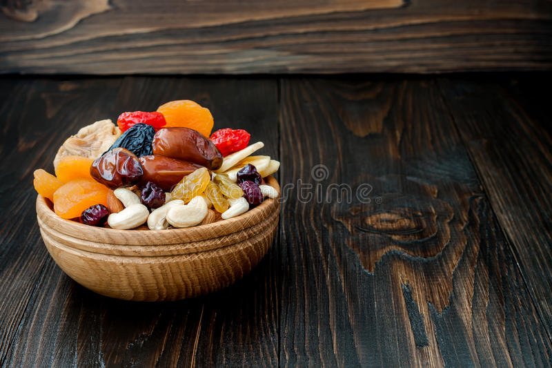 Mix of dried fruits and nuts on a dark wood background with copy space. Symbols of judaic holiday Tu Bishvat. Mix of dried fruits and nuts on dark wood stock images