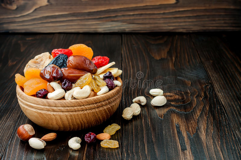 Mix of dried fruits and nuts on a dark wood background with copy space. Symbols of judaic holiday Tu Bishvat. Mix of dried fruits and nuts on dark wood stock image