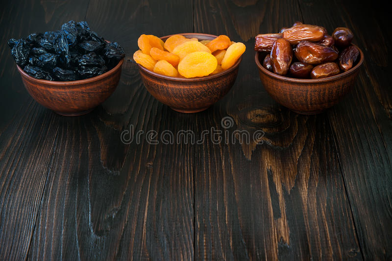 Mix of dried fruits and nuts on a dark wood background with copy space. Symbols of judaic holiday Tu Bishvat. Mix of dried fruits and nuts on dark wood royalty free stock images