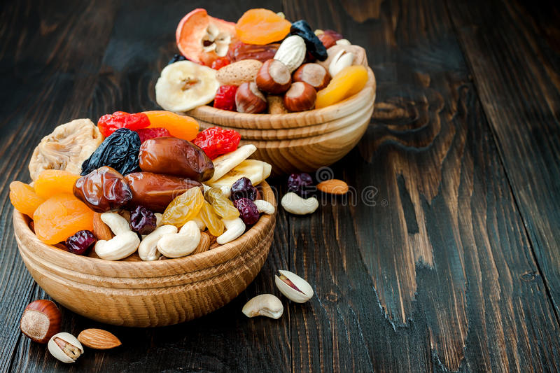 Mix of dried fruits and nuts on a dark wood background with copy space. Symbols of judaic holiday Tu Bishvat. Mix of dried fruits and nuts on dark wood stock photos